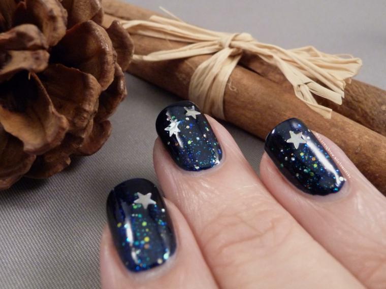 Decorazioni unghie natalizie, smalto colore blu glitter, decorazioni con stelle, pigna e bastoncino di cannella