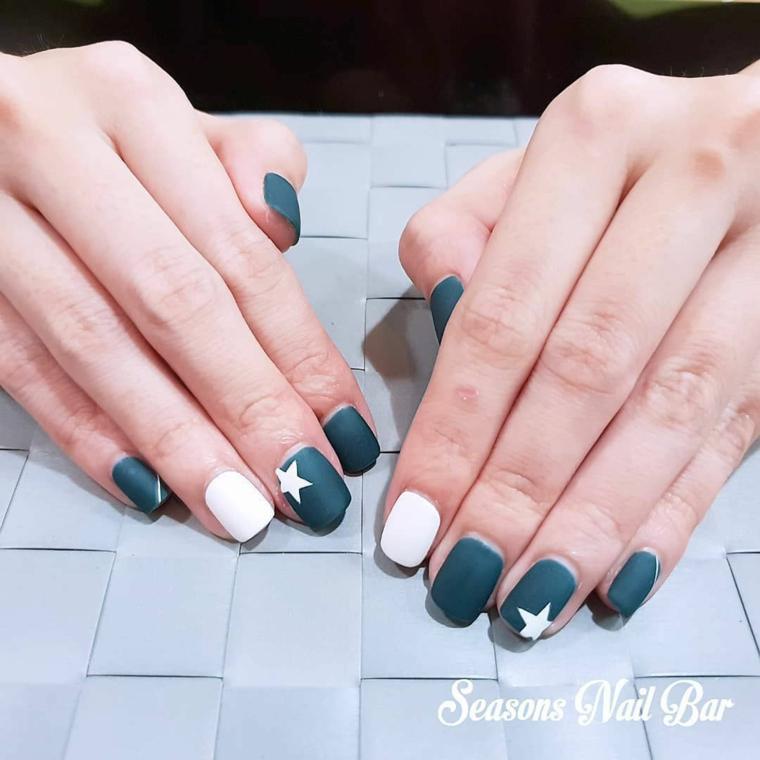 Unghie smalto di colore verde mat, accent nail smalto bianco, disegno stella, mani di una donna