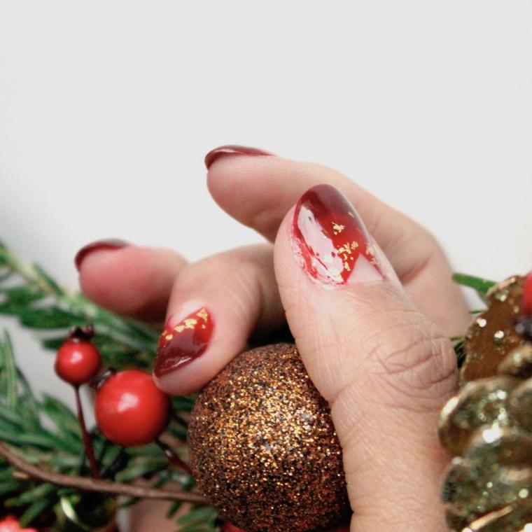Pallina glitter di Natale, unghie natalizie rosse e oro, rametti con bacche