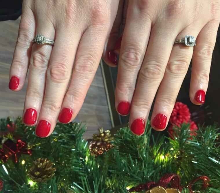 Unghie corte forma arrotondata, smalto di colore rosso, ghirlanda con pigne, anelli con diamanti