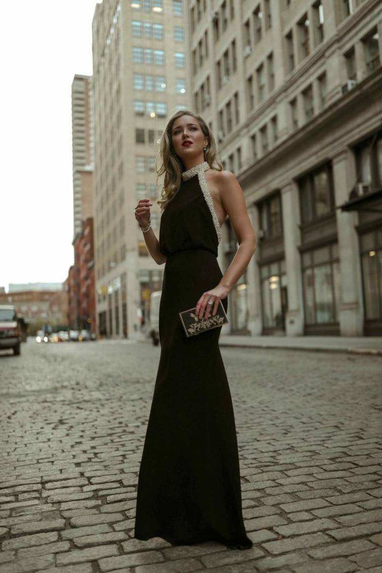 Vestito nero tubino, donna con capelli biondi mosso, abito con schiena scoperta, donna che cammina