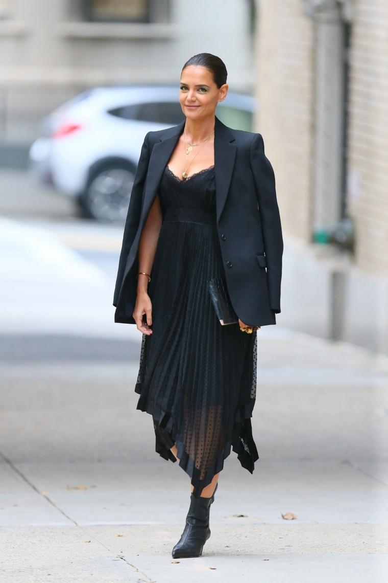 Abito nero plissettato, giacca elegante nera, donna che cammina, stivaletti neri con tacco