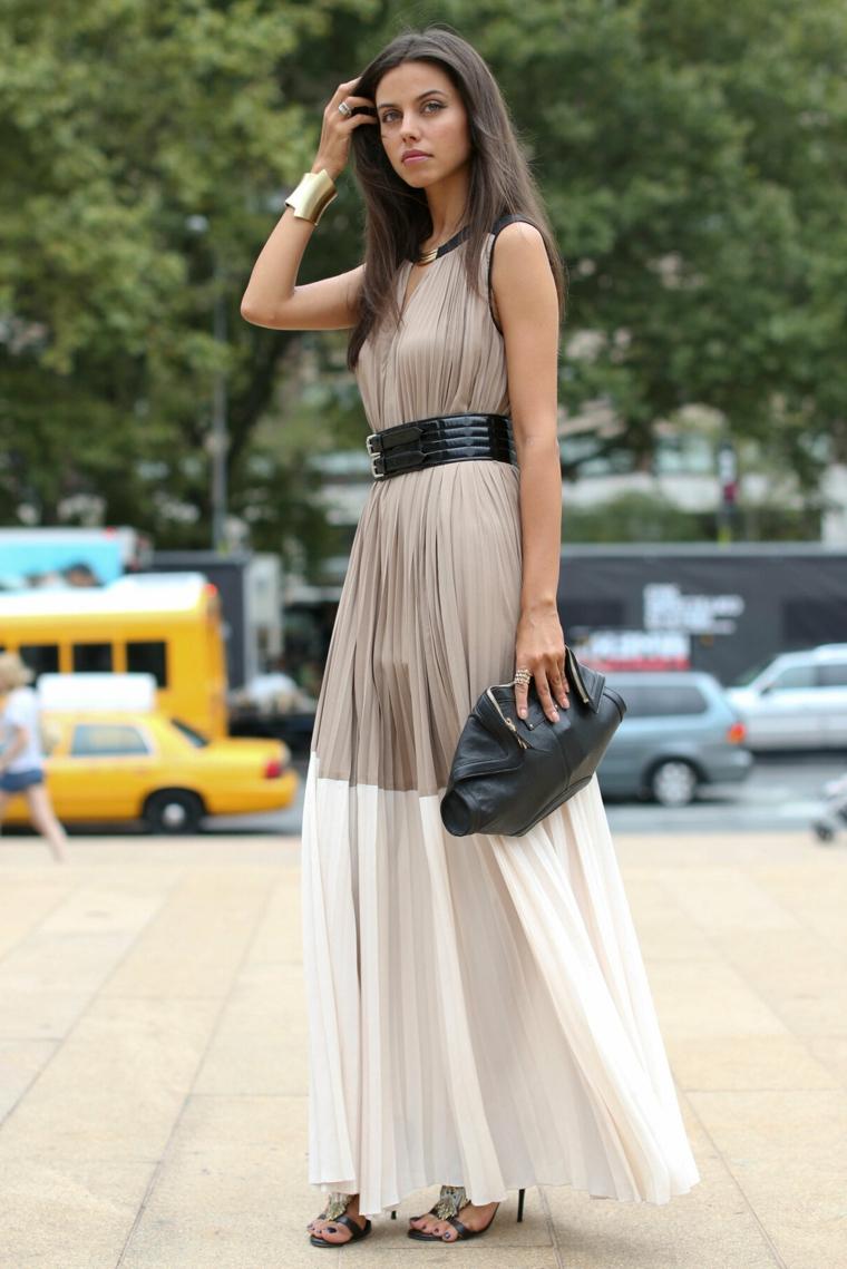 Abito di colore grigio e bianco, vestito plissettato lungo, abito con cintura in vita, donna che cammina
