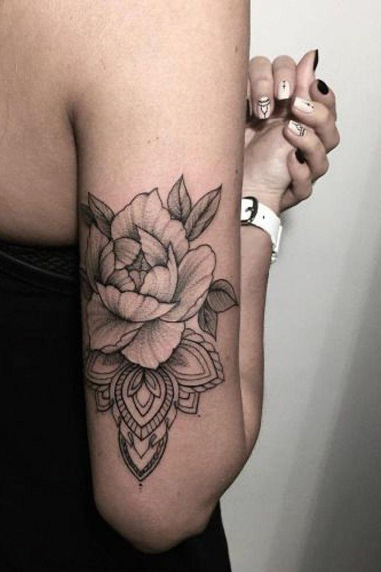 Tatuaggio sul braccio di una donna, tattoo con simboli del mandala e fiore di loto