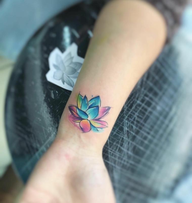 Simboli di rinascita e forza, disegno fiore di loto colorato, tatuaggio sul polso della mano