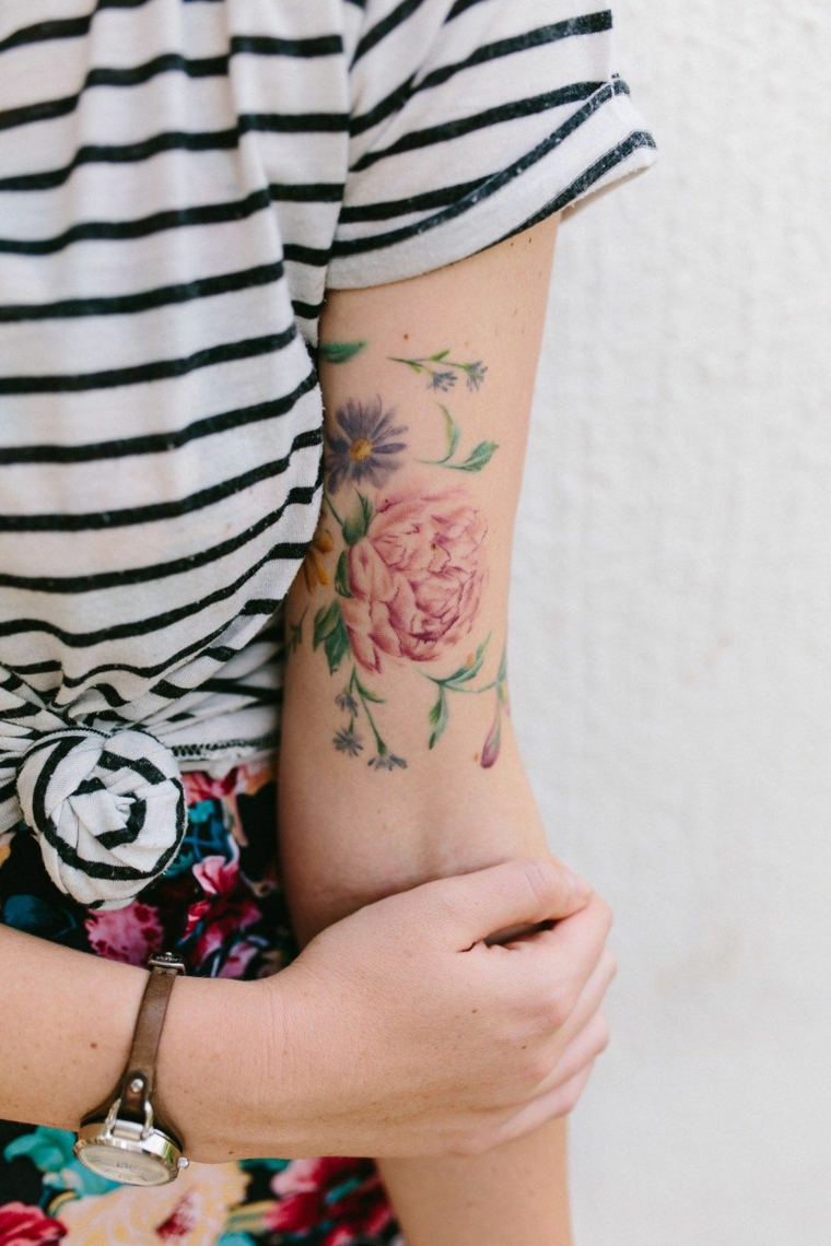 Fiore di loto significato, tatuaggio di un fiore colorato, tattoo sul braccio di una donna