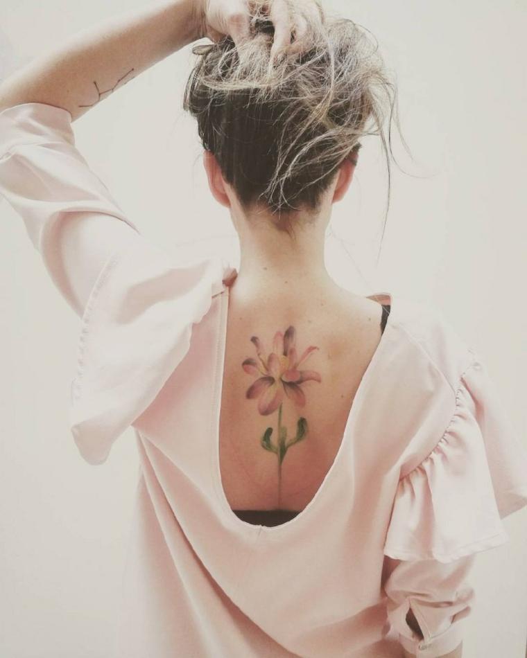 Simboli di rinascita e forza, donna con tatuaggio sulla schiena, lotus tatto colorato di rosa