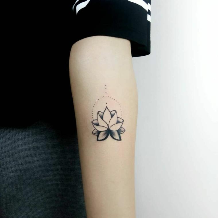 Simboli di rinascita e forza, disegno di fiore di loto, tatuaggio sull'avambraccio di una donna