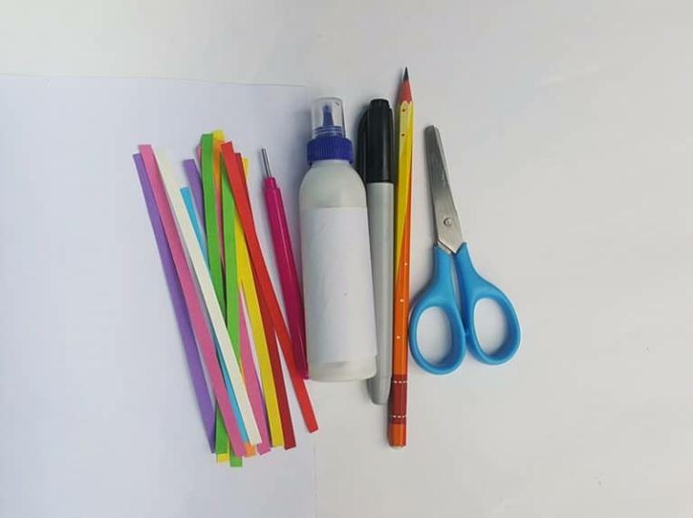 Strisce di carta colorata e colla, materiali necessari per unicorno stilizzato, strumento di metallo per piegare la carta