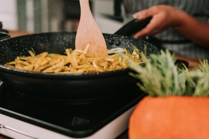 Come si fa la vellutata di zucca, padella con mestolo di legno, soffriggere la cipolla