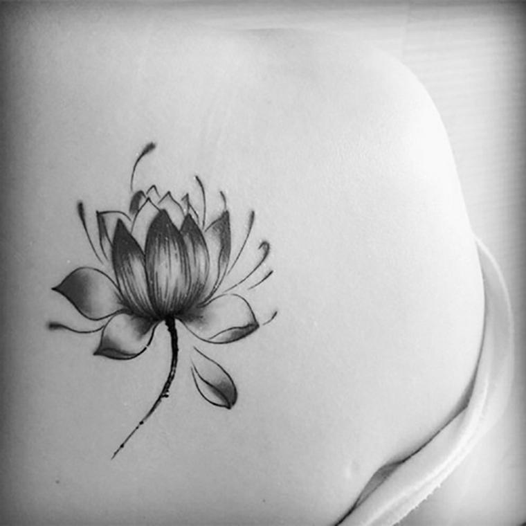 Donna con un tattoo sulla schiena, disegno di un fiore di loto, tattoo con simboli del mandala