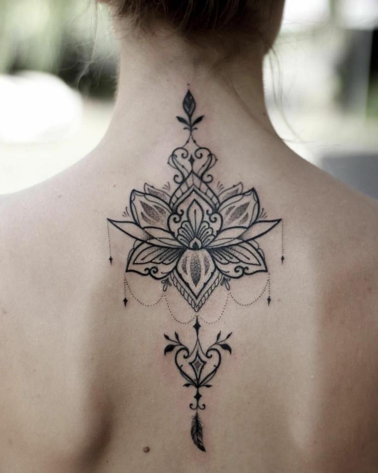 Donna con tatuaggio sulla schiena, tattoo con simboli del mandala, disegno di un fiore di loto