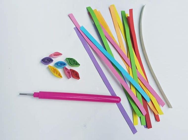 Strisce di carta colorata e piegata, strumento di metallo per piegare la carta, immagini unicorni