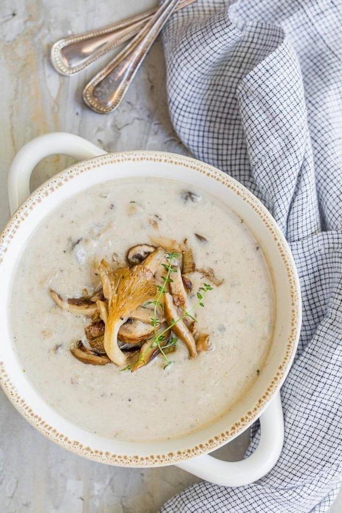 Minestra frullata con funghi, pentola con vellutata di verdure, piatto con cucchiai