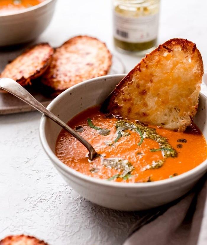 Pezzo di pane inzuppato nella vellutata, zuppe autunnali, vellutata di pomodoro