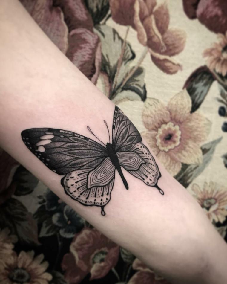 Farfalla stilizzata, tattoo sull'avambraccio di una donna, farfalla colorata di nero