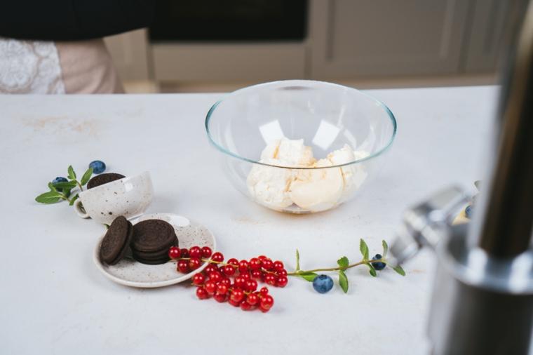 Ricetta cheesecake fredda, ciotola di vetro con mascarpone, piattino con biscotti oreo