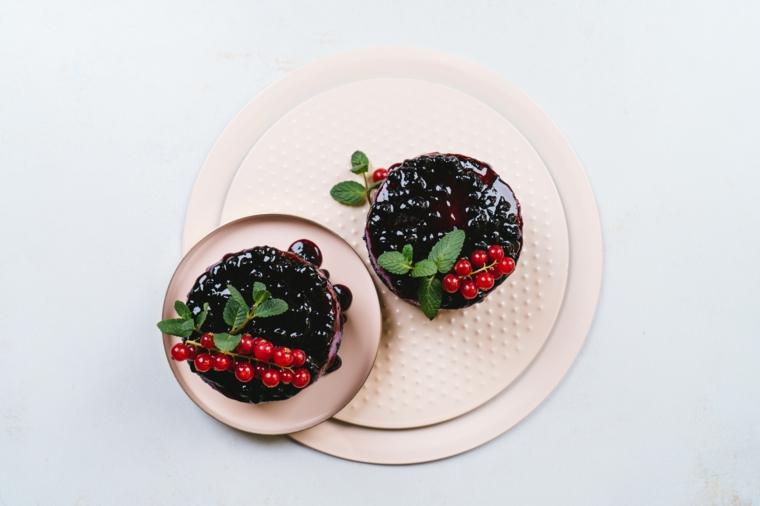 Due cheesecake con marmellata di mirtilli, cheesecake decorata con bacche e foglie di menta