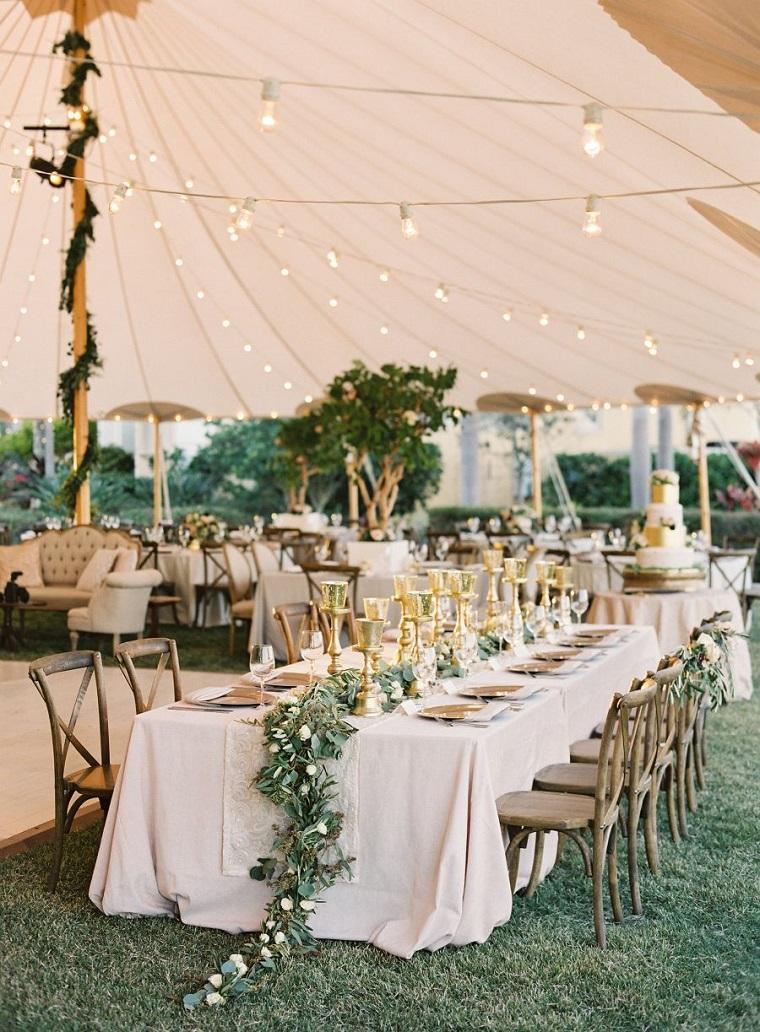 Centrotavola con ghirlanda di rametti e foglie, fili con lampadine attaccate, matrimonio fai da te economico