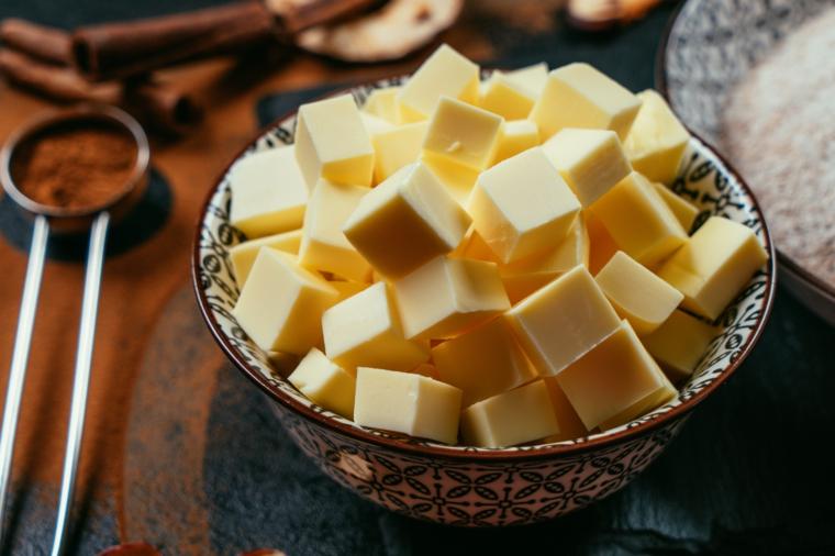 Torta di mele americana, ciotola con cubetti di burro, cucchiaio con cannella in polvere