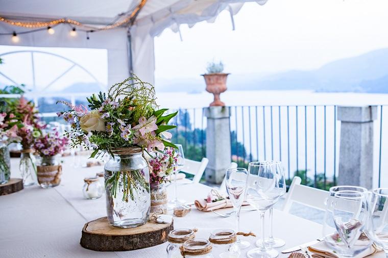 Tavola apparecchiata con centrotavola di fiori, matrimonio su un lago
