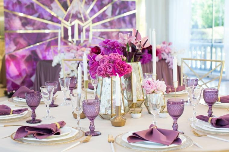 Tavola apparecchiata con bicchieri e piatti, vaso di vetro con fiori viola