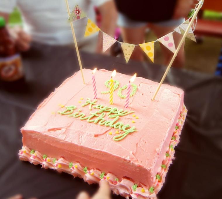 Torta di compleanno estiva, torta con panna montata di colore rosa, topping torta con ghirlanda