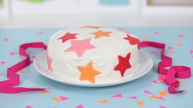 Torta di compleanno estiva, torta rotonda con panna montata e stelle di pasta di zucchero