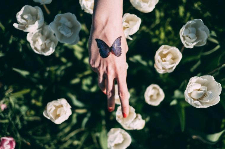 Farfalla stilizzata, disegno farfalla nera sulla mano di una donna, rose con petali bianchi