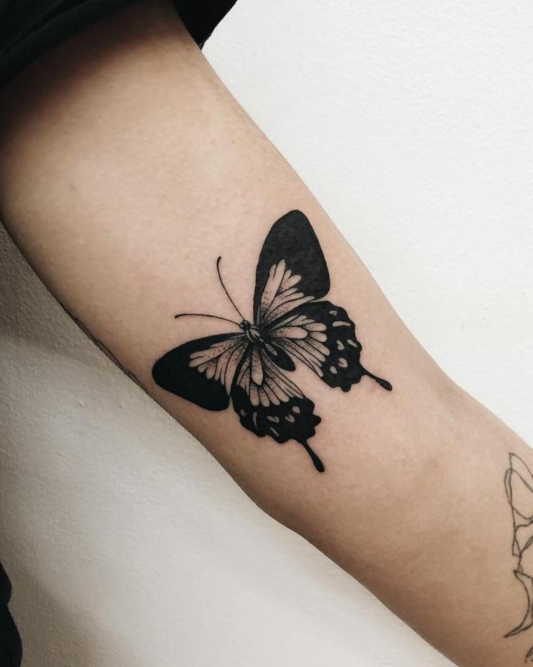 Farfalla significato, disegno di una farfalla colorata di nero, tattoo sul braccio