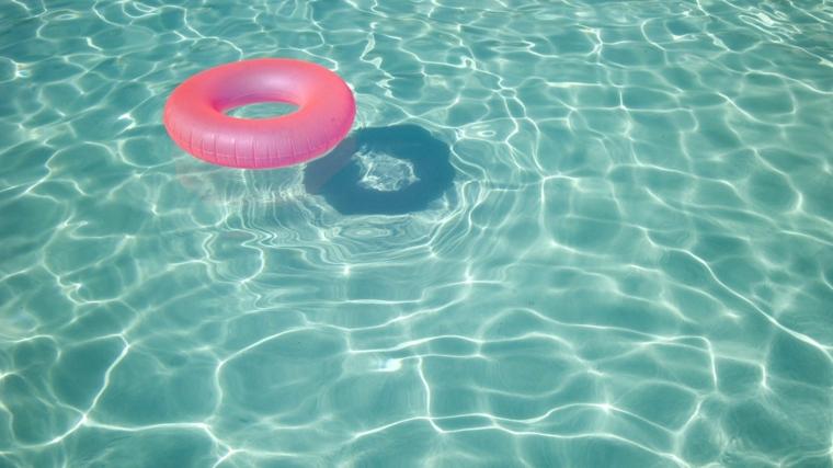 Foto di una piscina con salvagente rosa, ciambella rosa nell'acqua della piscina, foto desktop computer