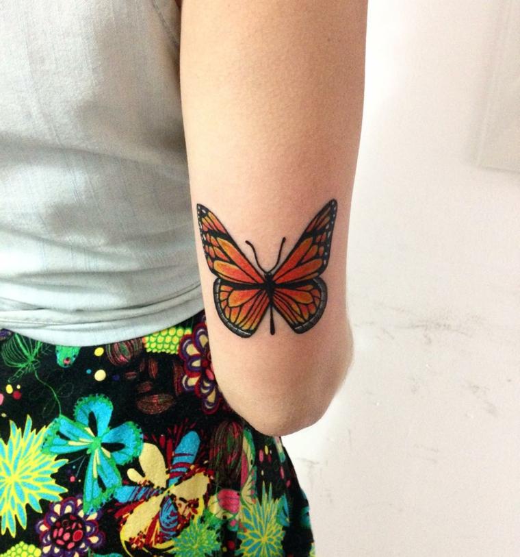 Tatuaggio farfalla, disegno colorato di una farfalla arancione, tattoo sul gomito di una donna