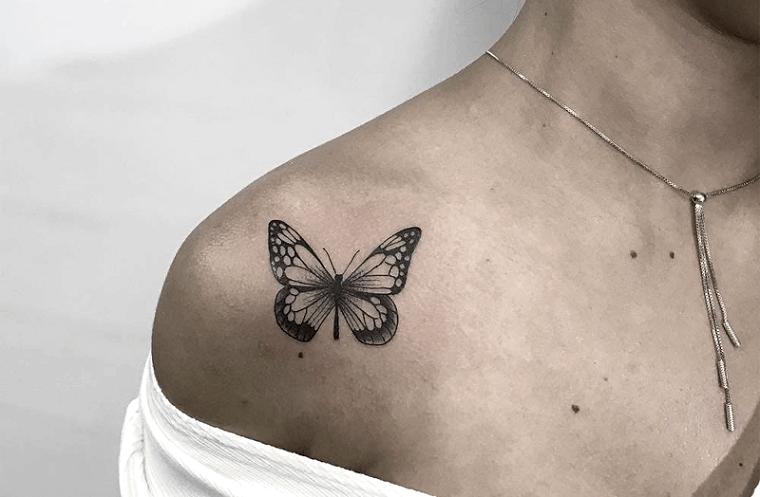 Farfalla stilizzata, disegno di una farfalla sulla spalla di una donna, collana in oro sul collo di una donna