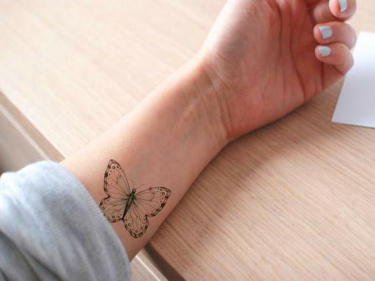 Farfalla significato, avambraccio di una donna con tatuaggio di una farfalla