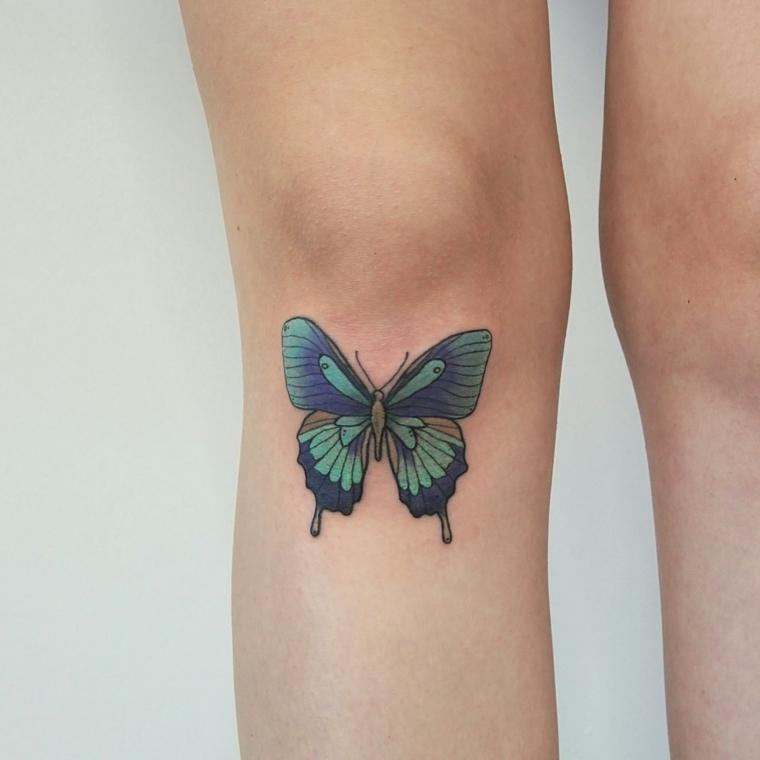 Farfalla tattoo, disegno di una farfalla colorato di blu, tatuaggio sul ginocchio di una donna