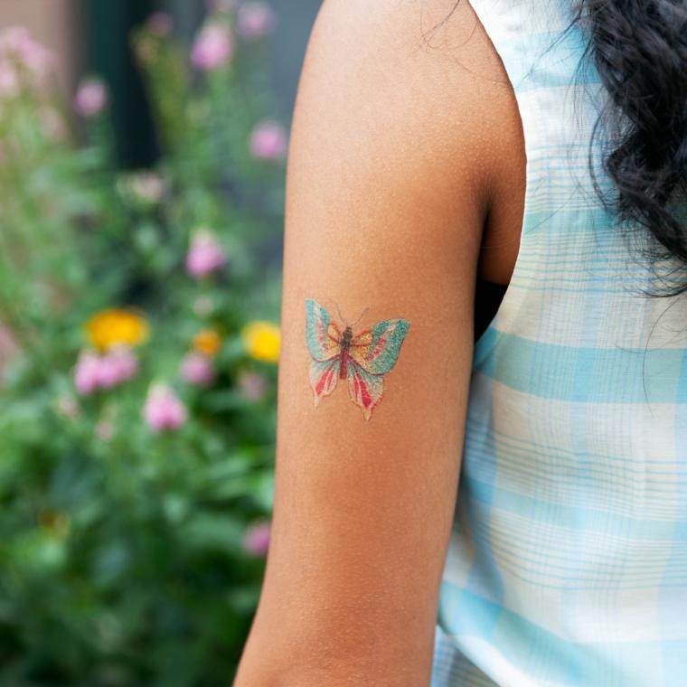 Farfalla stilizzata, disegno colorato di una farfalla, tatuaggio temporaneo braccio donna