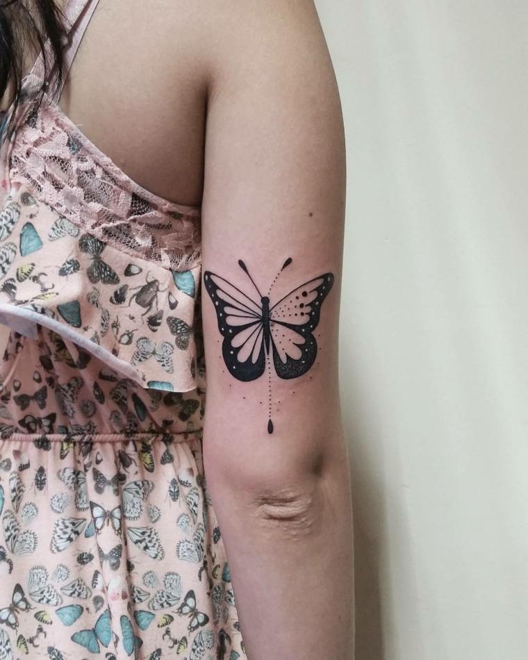 Farfalla stilizzata, tatuaggio sul gomito di una donna, disegno di una farfalla