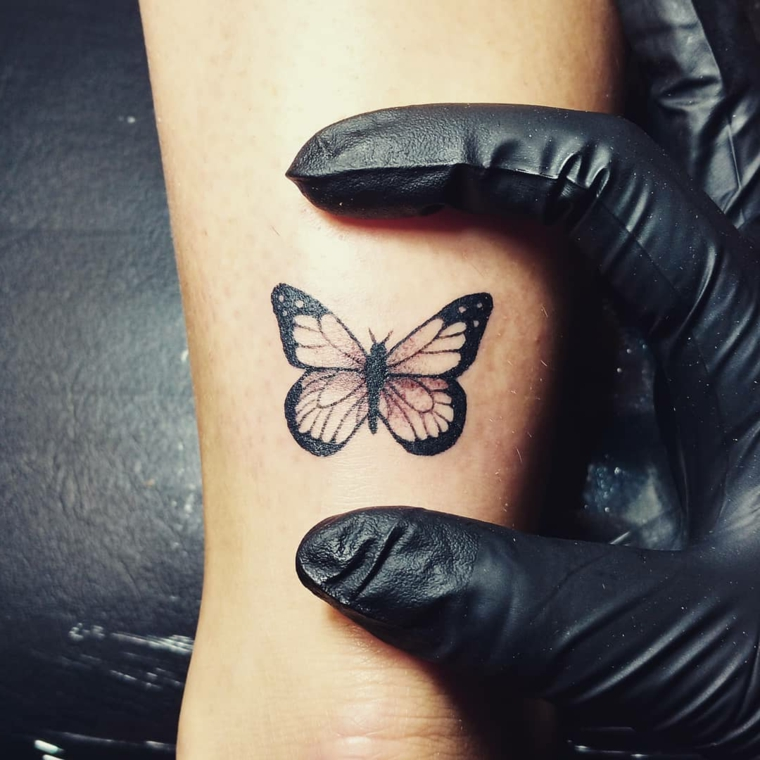 Farfalla stilizzata, tatuaggio sulla caviglia di una donna, tatuatore con guanti neri