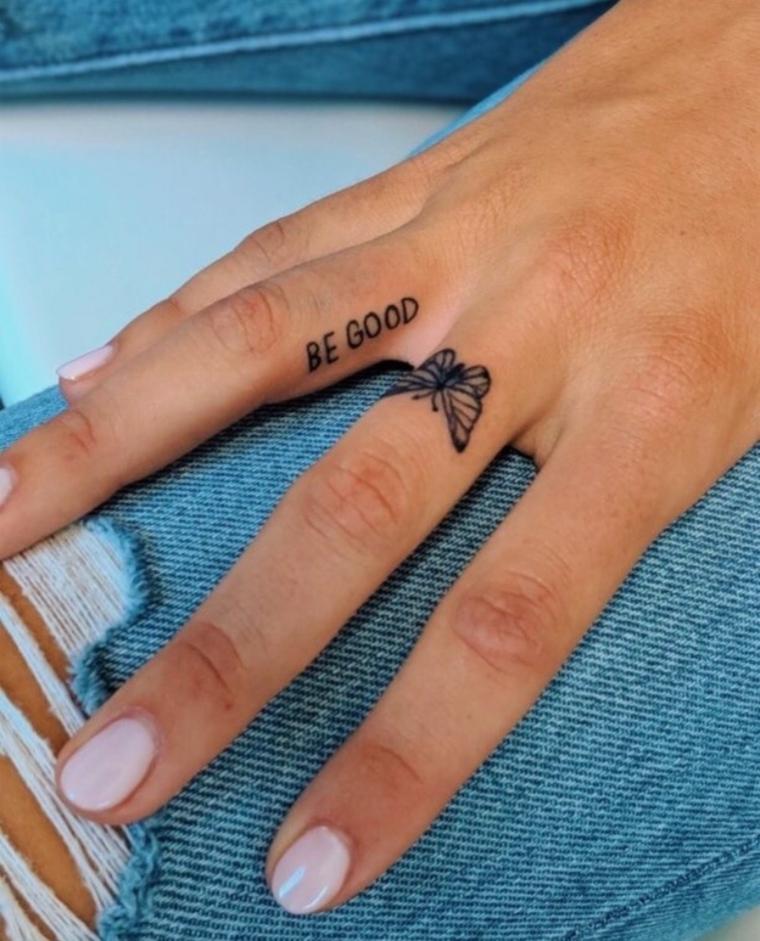 Tatuaggio farfalla, dito di una donna con tattoo scritta, disegno farfalla come tatuaggio
