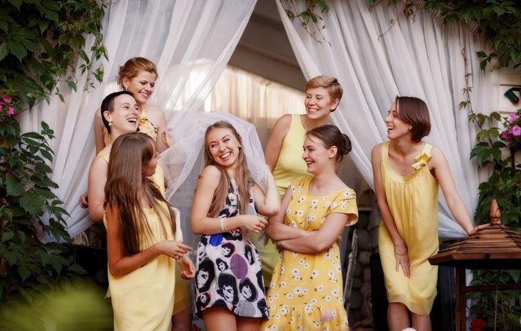 Sposa con velo bianco, damigelle della sposa con vestiti di colore giallo