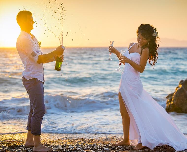 Sposa e sposo sulla spiaggia, uomo e donna che aprono bottiglia di spumante