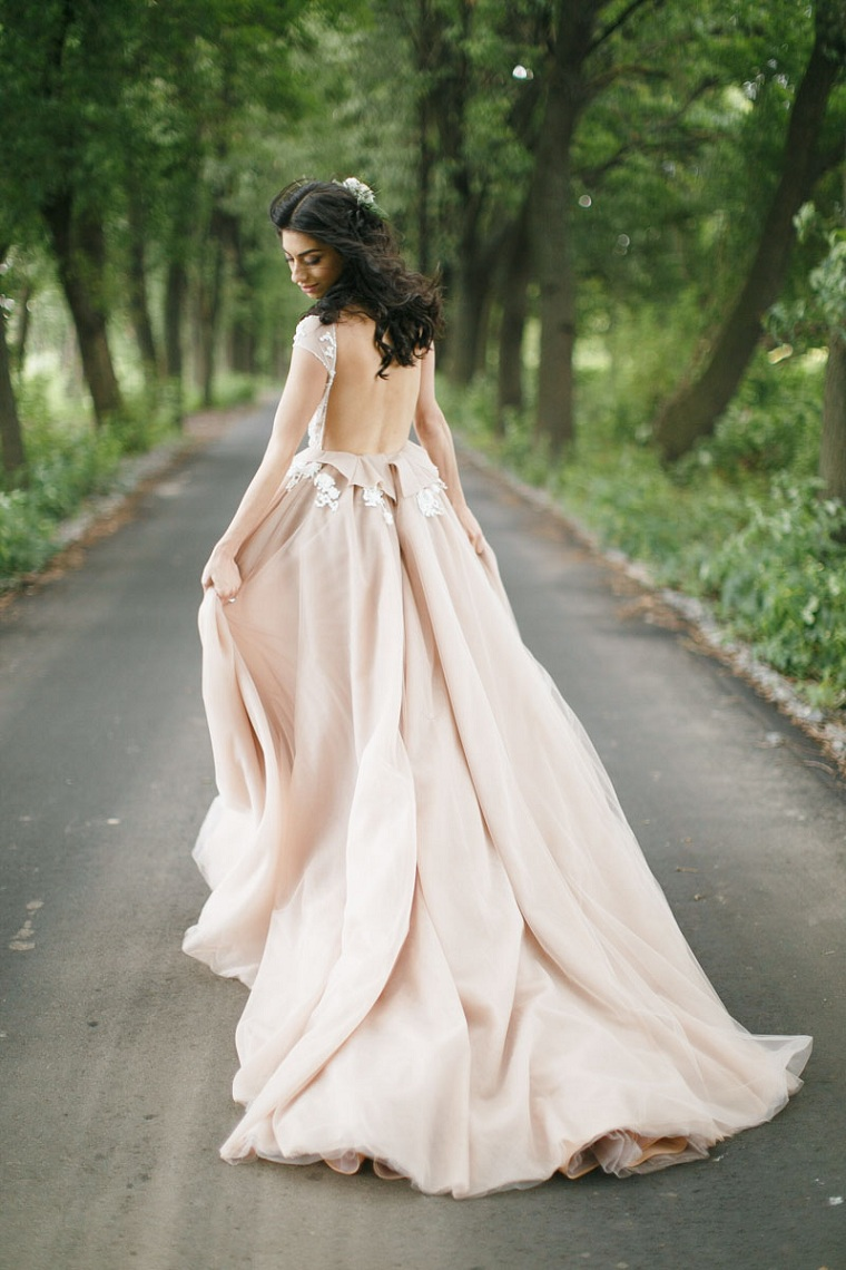 Sposa con un abito di colore pesca, donna che cammina su un sentiero in un bosco