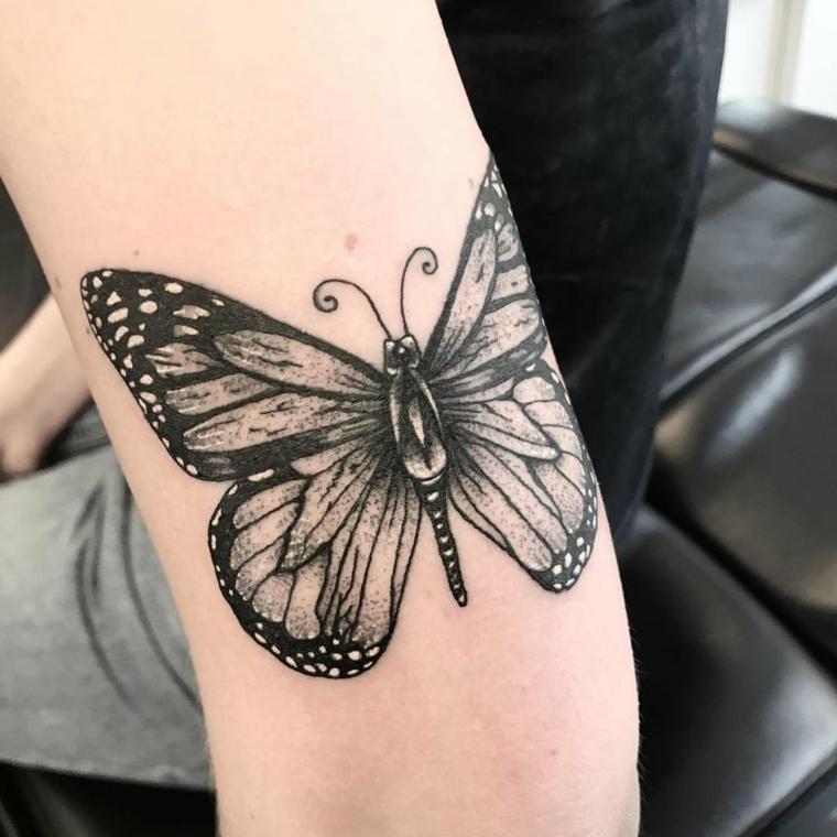 Farfalla tattoo, disegno colorato di nero di una farfalla, tattoo sul gomito di una donna