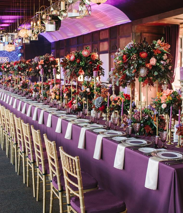 Tavola apparecchiata con tovaglia di colore viola, centrotavola con fiori e candele