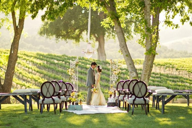 Donna e uomo sposi sotto un arca, giardino con prato verde con sedie e tavolo