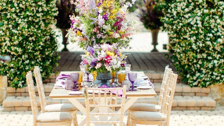 Come si organizza un matrimonio, tavolo quadrato di legno con un centrotavola di fiori