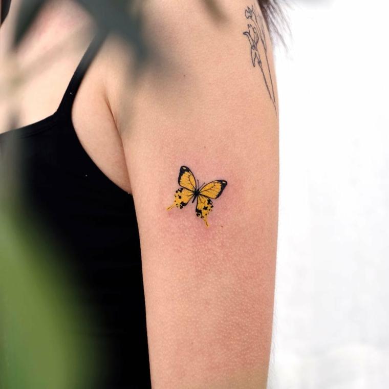 Disegni farfalle colorate, tattoo di una farfalla sul braccio di una donna