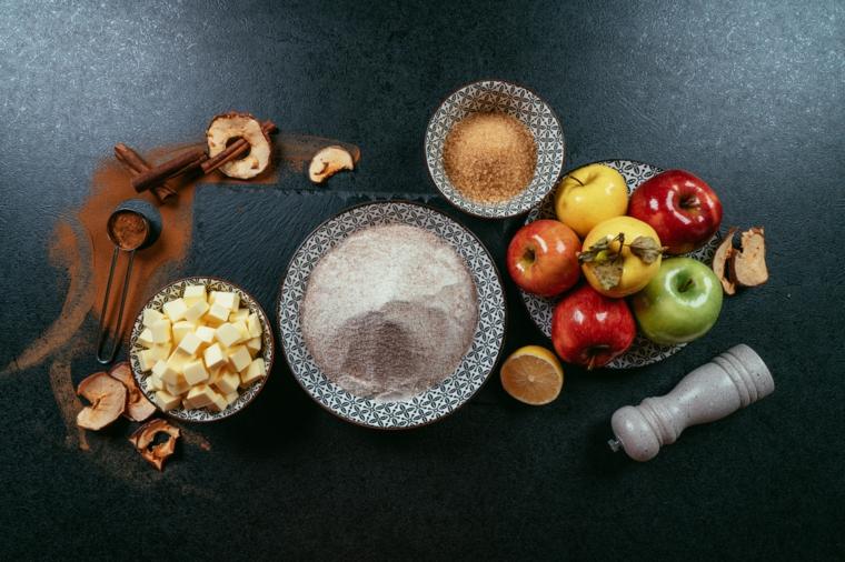 Ciotole con ingredienti per crostata, ricetta crostata di mele, piatto con mele verdi e rosse