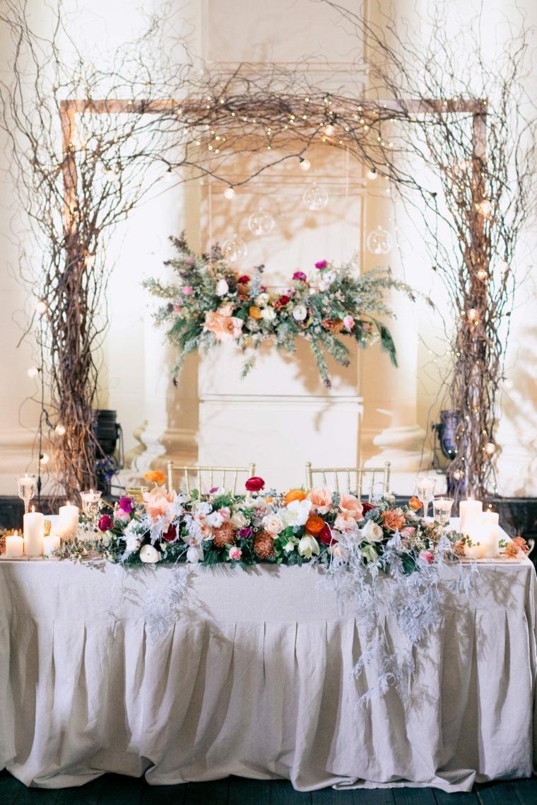 La tavola degli sposi con centrotavola di fiori, arca di legno con rami e luci, preparativi matrimonio