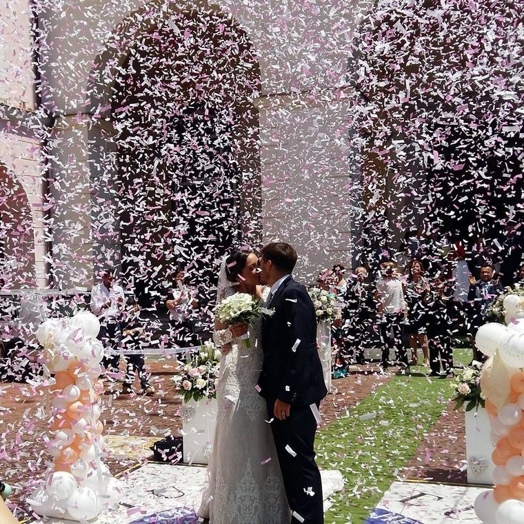 Sposi che si baciano sotto coriandoli, decorazioni matrimonio con palloncini
